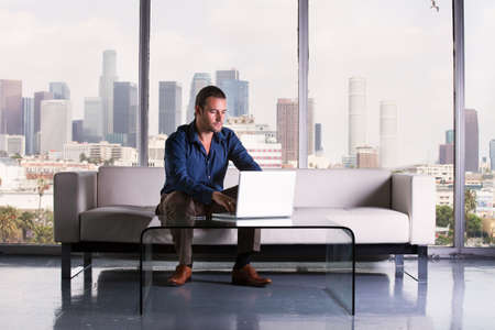 Handsome casual business man working in a Penthouse Suite with Los Angeles Skyline behind him photo