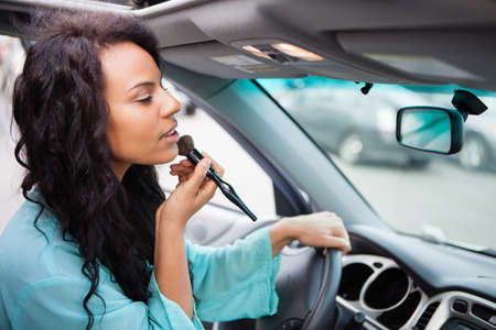 Attractive young woman touching up her make up in a Car looking in the rear view mirror photo