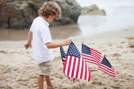 Cute boy with American Flags on the beach in Malibu California photo