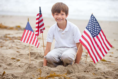 Attractive boy with American Flags on the beach in Malibu California photo