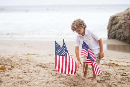 10 11 years: Cute boy with American Flags on the beach in Malibu California Stock Photo