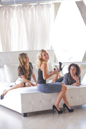 Young Group of Friends talking and laughing on a Hotel Bed Penthouse Suite photo