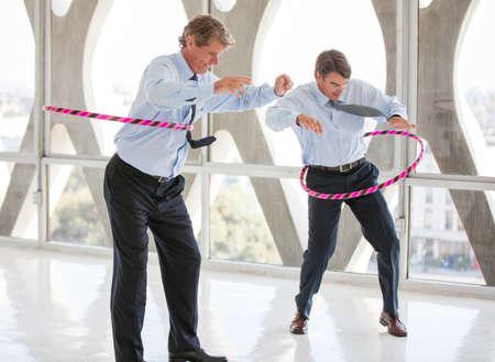 office break: Hombres de negocios tener un concurso de hula en una moderna oficina para obtener ideas que fluyen