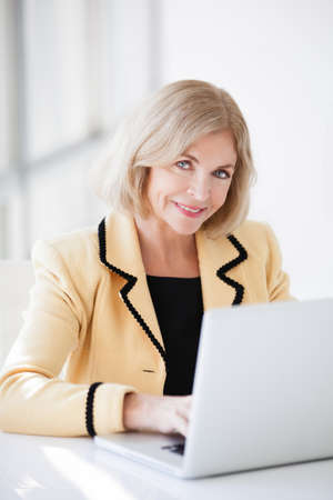Pretty woman in her fifties on a computer looking at camera