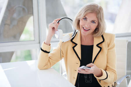 Beautiful fifty year old woman enjoying music with her noise canceling headset