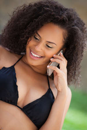 Beautiful Girl Smiling while talking on her cell phone summer vacation photo