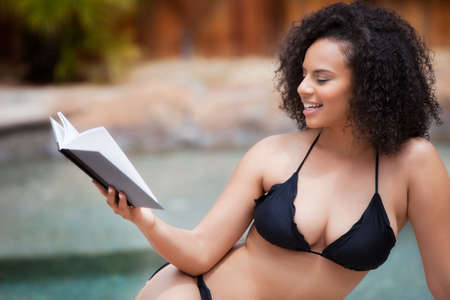 Pretty woman in a Bikini holding a book at the pool photo