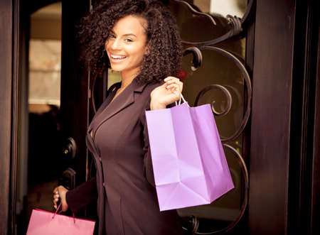 Beautiful young woman smiling holding colorful shopping bags photo