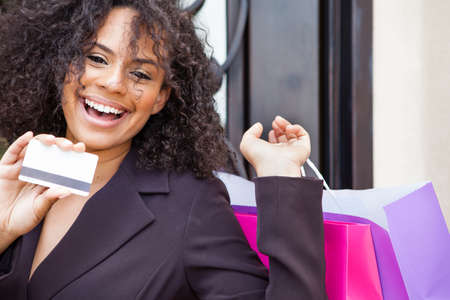 Beautiful young woman smiling holding a credit card and colorful shopping bags
