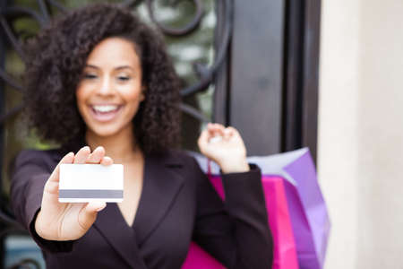 Pretty woman smiling holding a credit card focus is on the card photo