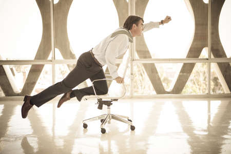 superman: Good looking Business man Flying on a chair as if to be superman Stock Photo