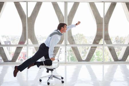 Apuesto hombre de negocios que vuela en una silla como si fuera a ser Superman