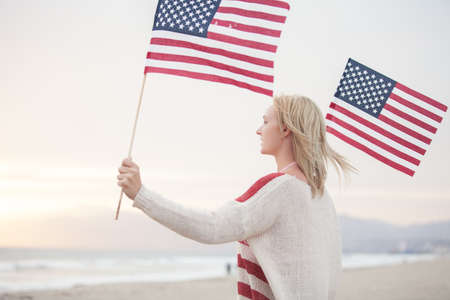 Pretty Young Woman at the Beach holding American Flags facing the ocean photo