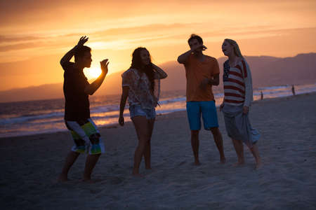 union beach: Group of young people dancing on the Beach at Sunset on 4th of July