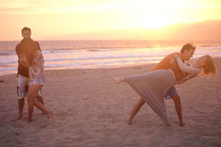 union beach: Group of Friends in their twenties dancing on the Beach at Sunset in Venice Beach California