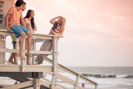 Young Group of Friends at the Beach on the Lifeguard stand in Southern California photo