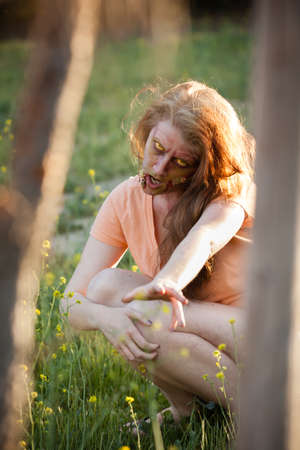 scarry: Woman Zombie reaching out in daylight Stock Photo
