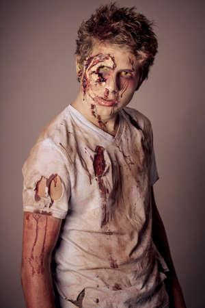 reanimated: Sneering Teenager Zombie in torn bloody shirt