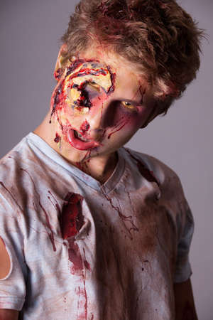 malevolent: Sneering Teenager Zombie in torn bloody shirt