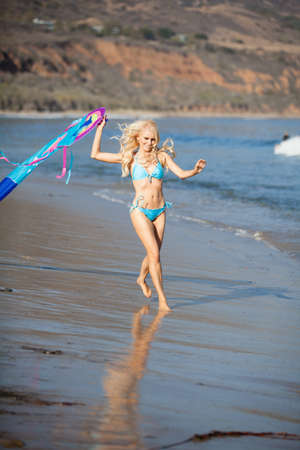 flying kite: Pretty young woman running with a kite on the beach in California