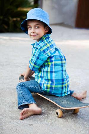 boy skating: Cute child sitting on Skateboard wearing a blue hat Stock Photo