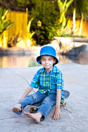 Cute child sitting on Skateboard wearing a blue hat photo