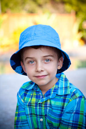 boys only: Portrait of a cute boy in a blue hat during summer