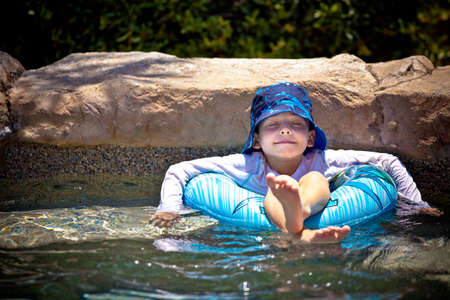 Young boy floating in a inner tube eyes closed in a blissful state Stock Photo