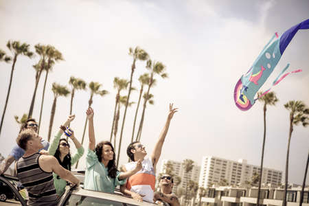 Group of young people flying a kite from their Sunroof in Venice Beach California photo