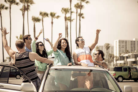 Group of young people flying a kite from their Sunroof in Venice Beach California