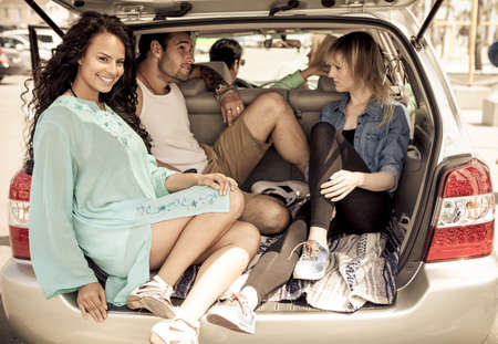Beautiful Woman with friends in the back of an SUV photo