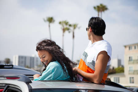 getting away from it all: Couple in Venice Beach California out the top of the sun roof of their SUV