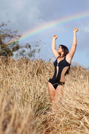 Beautiful Young Woman under a Rainbow in a field of tall grass Hawaii photo