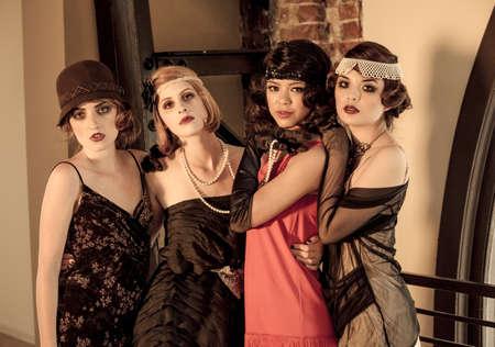 Beautiful Vintage Women celebrating at a gathering posed looking at camera Standard-Bild