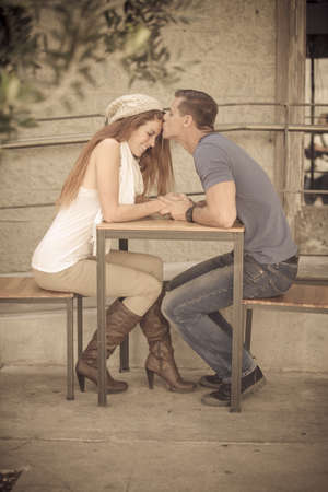 girl boots: Young Couple kissing at a cafe table in the city of Los Angeles, California Stock Photo
