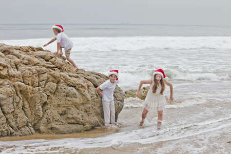 Kinder am Strand in Weihnachten HatsMalibu, Kalifornien photo