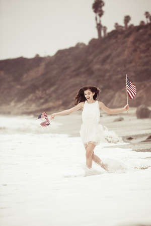 Beautiful Teen Girl with American flags walking on the Beach in Malibu photo
