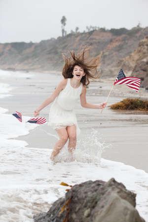 Beautiful Teen Girl with American flags walking on the Beach in Malibu photo