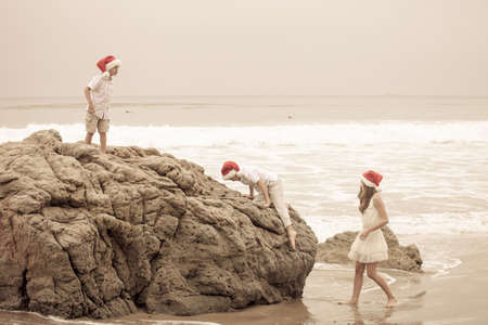 Kinder am Strand in Weihnachts HatsMalibu, Kalifornien photo