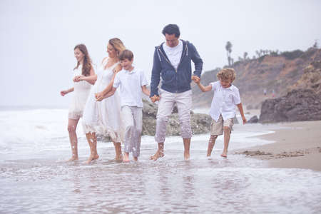 Beautiful family walking on a beach in Southern California