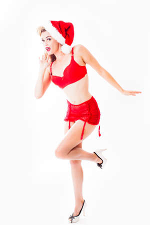 Pretty blonde woman in red lingerie and Santa Clause hat  in a sexy pose Stock Photo