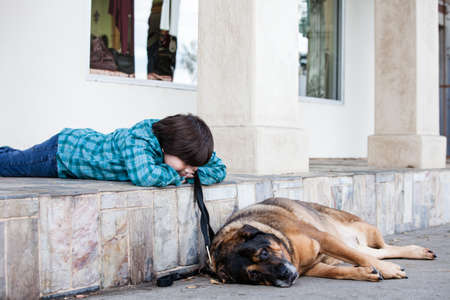 A 10 yeqr old boy and his doy lying down on the sidewalk