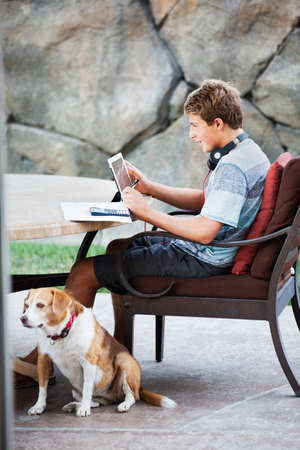 beagle mix: Teenager on a touch pad and headphones doing homework with his dog Stock Photo