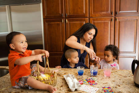 Young Family coloring easter eggs in Kitchen photo