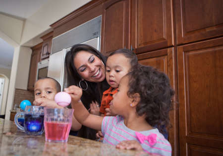 daycare: Young Family coloring easter eggs in Kitchen