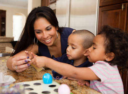 Young Family coloring easter eggs in Kitchen
