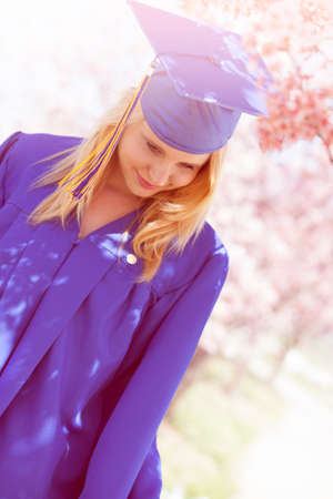 Graduation Pretty Blonde woman looking down reflecting on her journey photo