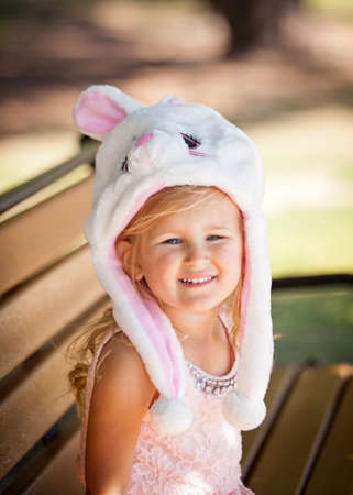 Cute  young girl in a Bunny hat smiling in the park photo