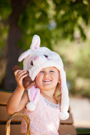 Cute  young girl in a Bunny hat smiling in the park holding a chocolate Easter Bunny photo