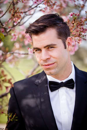 Good looking guy with a bow tie under a cherry tree in bloom